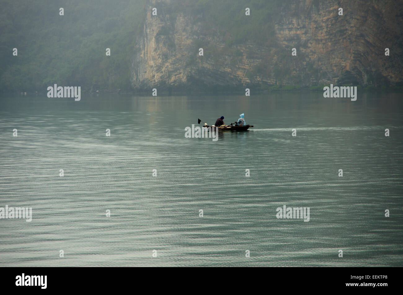 Woman in blue rain tarp rows very tiny boat as man sit in bow and fishes - Stock Image