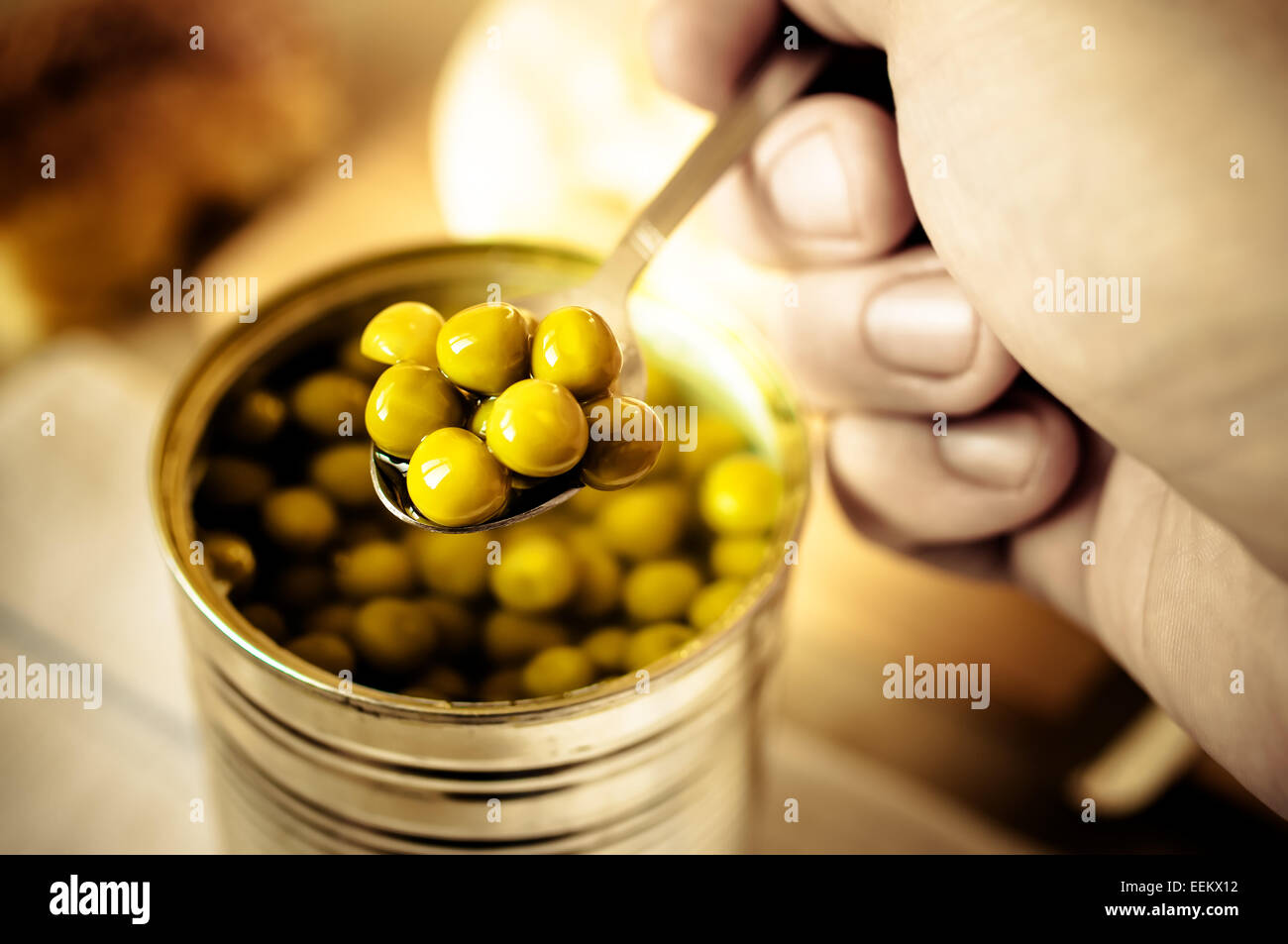 Man with a spoon takes canned peas - Stock Image