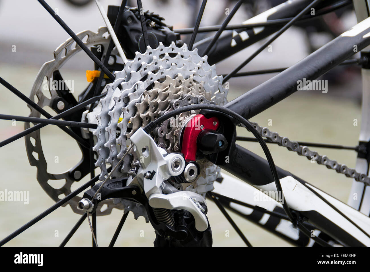 The rear side of a mountain bike with detail on sprockets , brakes and rear shifter system - Stock Image