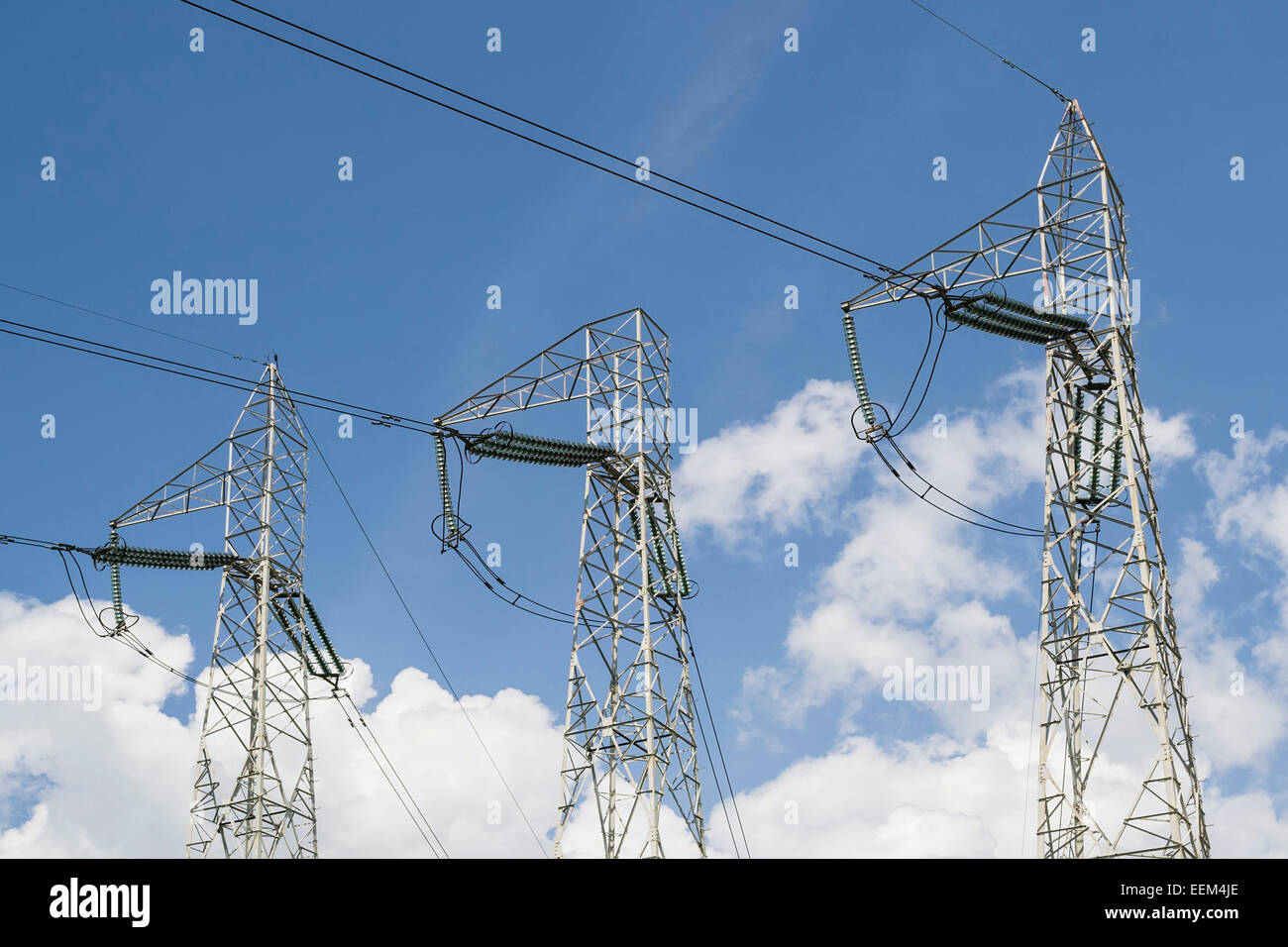 Three metallic towers for high-voltage  electrical energy transmission - Stock Image