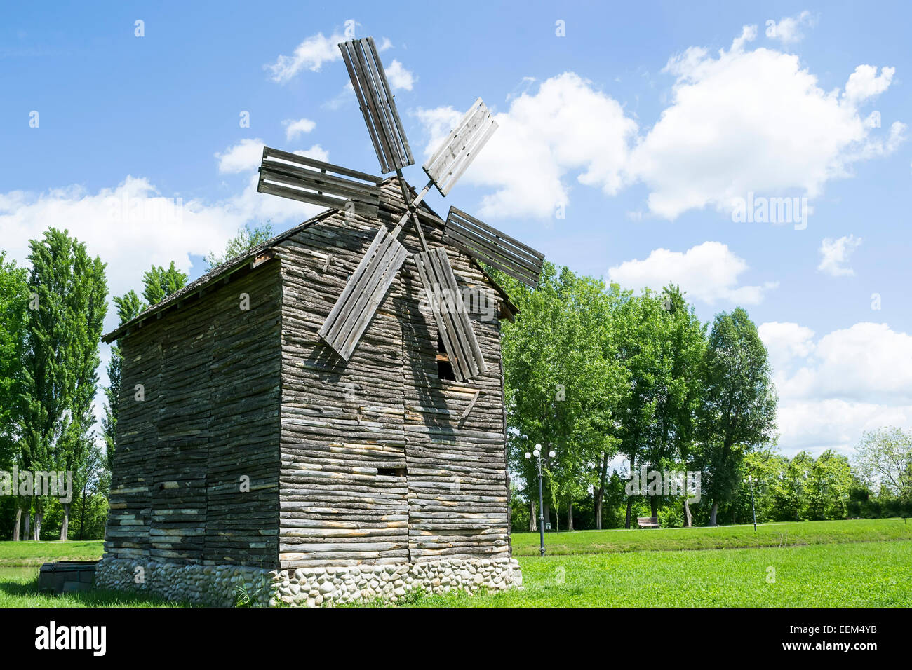 Old wooden windmill with stone foundation being on display in a park - Stock Image