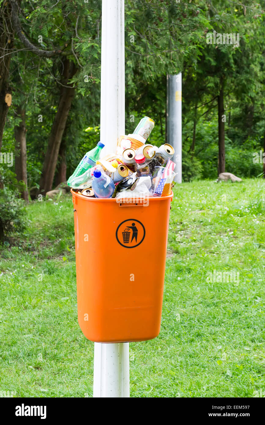 Trash can attached to a pole , full with garbage after a week-end in the park - Stock Image