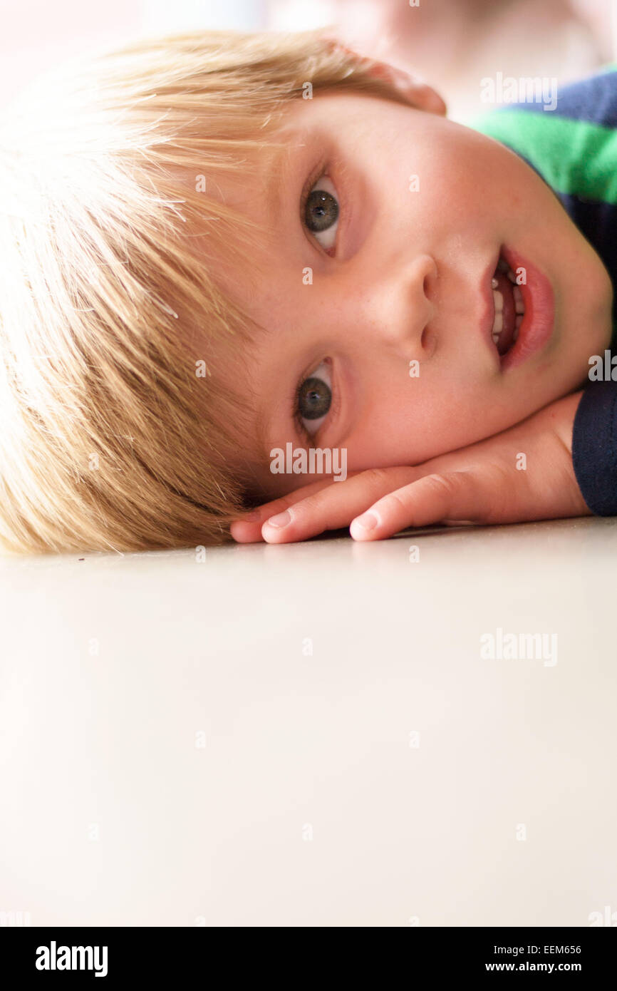Portrait of young boy (4-5) laying down - Stock Image
