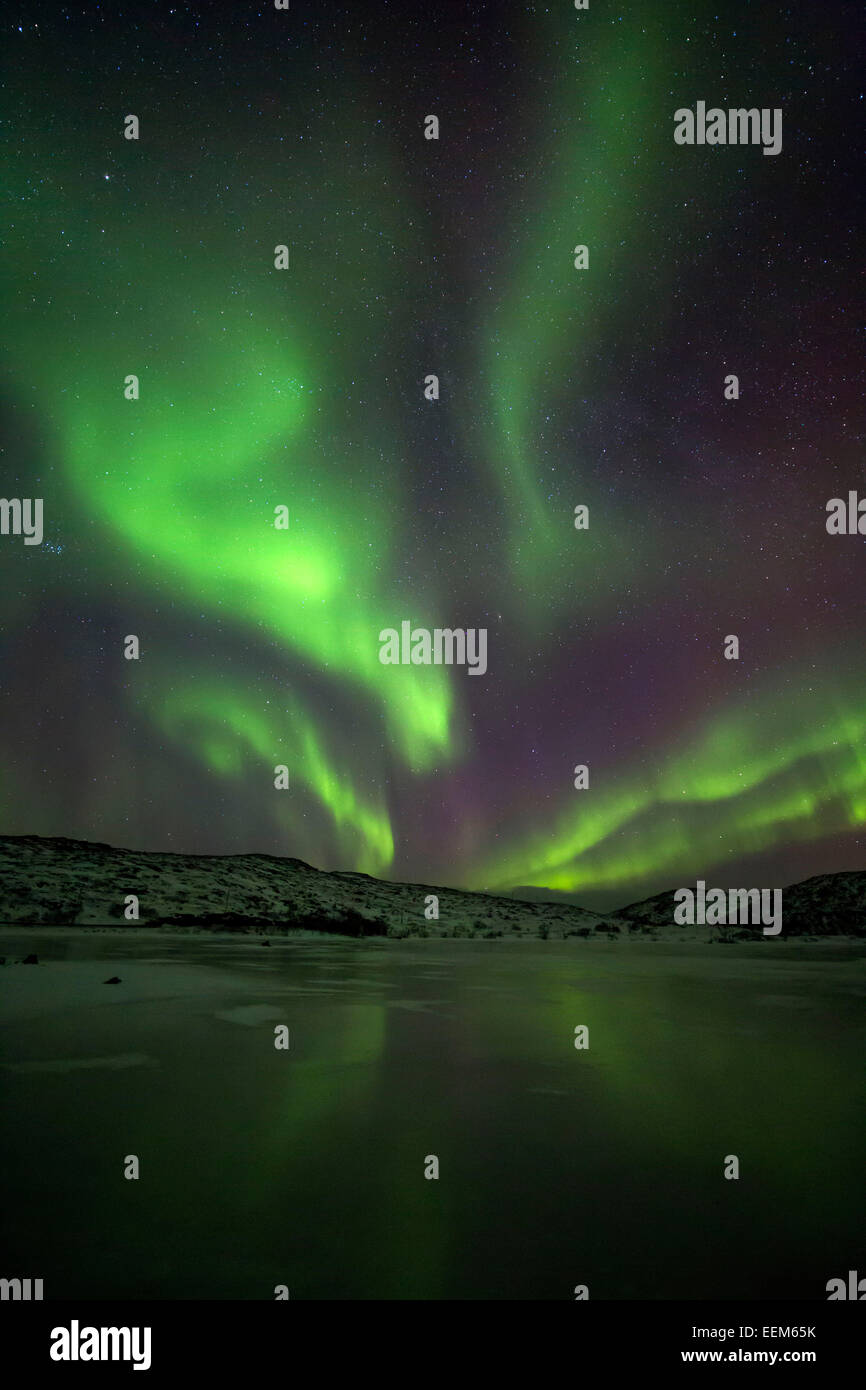 Norway, Tromso, Northern lights over frozen fjord - Stock Image