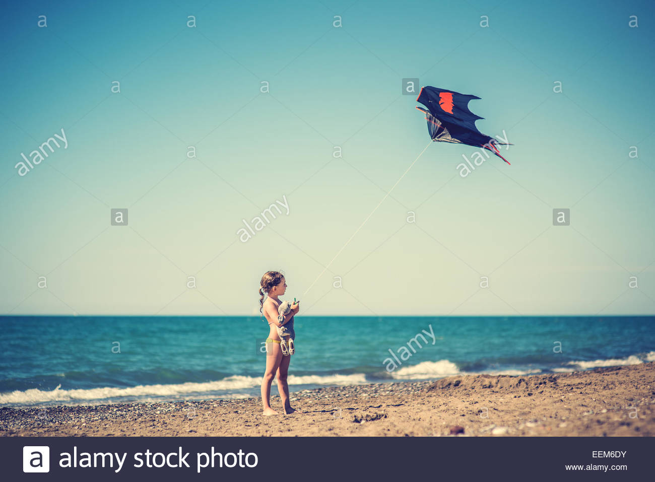 Girl flying kite on sandy beach - Stock Image