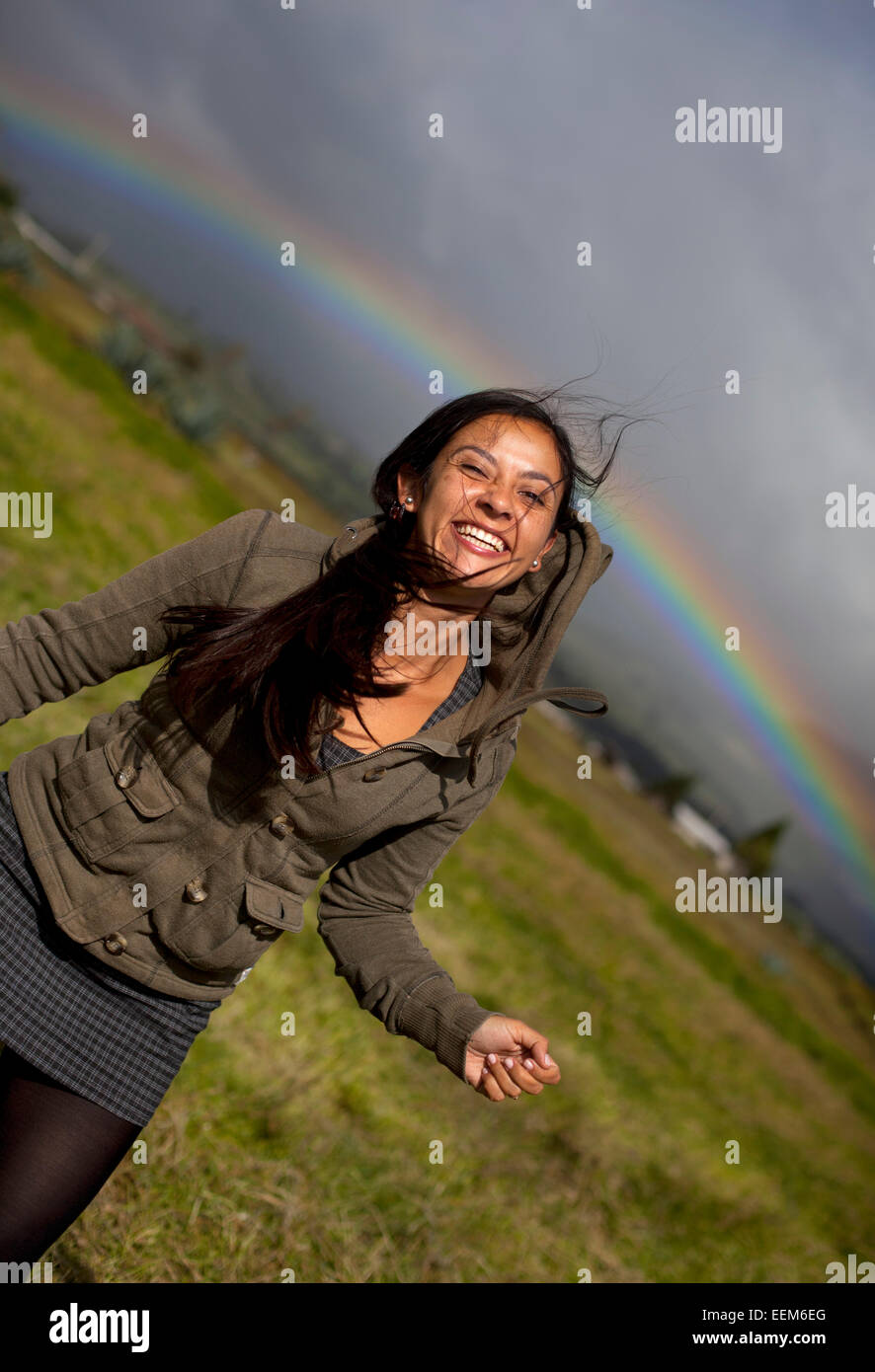 Ecuador, Cayambe, Smiling woman with rainbow in background, Cayambe, Ecuador - Stock Image