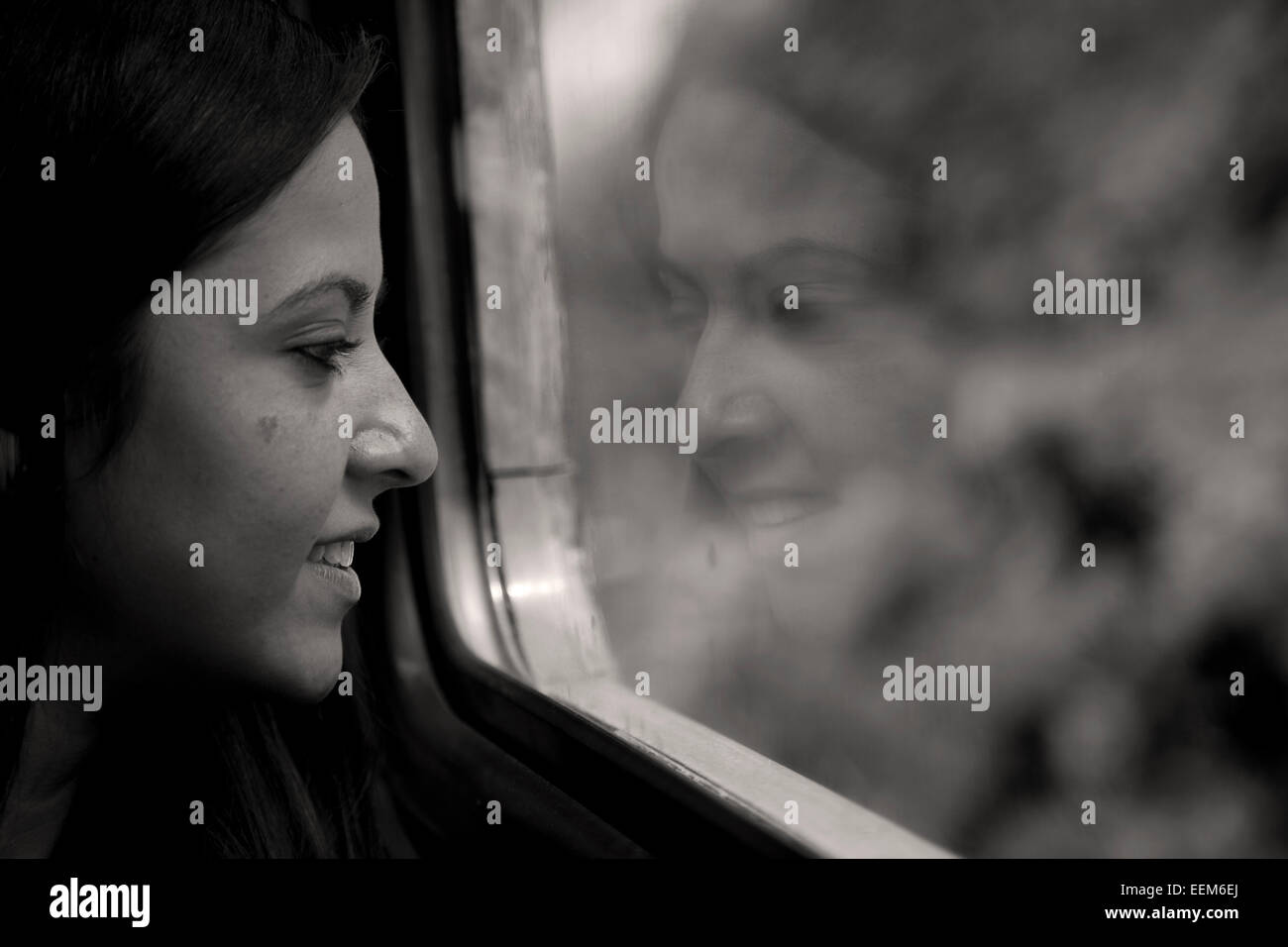 woman sitting on a train looking out of the window - Stock Image