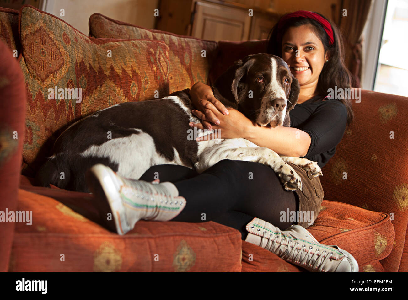 Woman sitting on couch with her dog Stock Photo