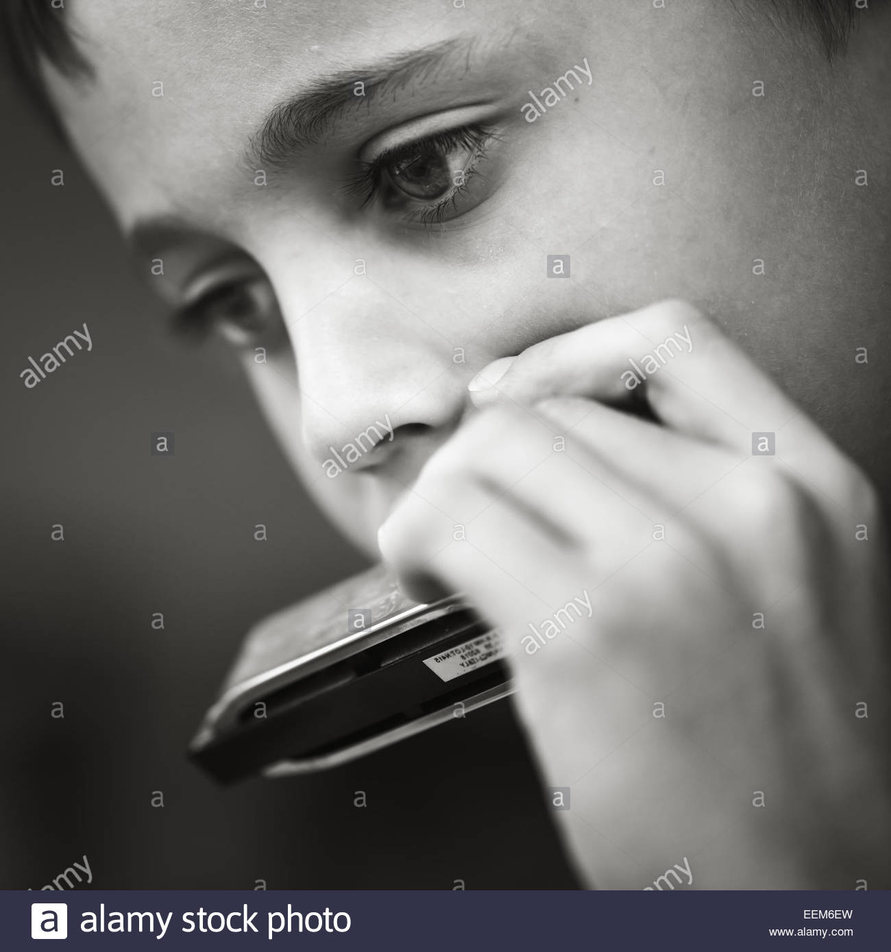 Close-up of boy (8-9) playing harmonica - Stock Image