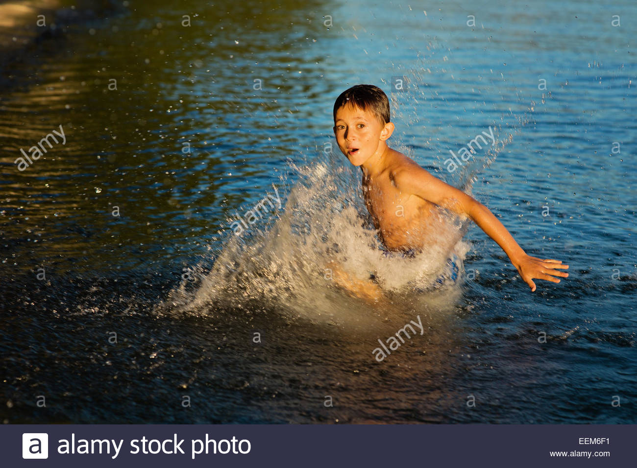 Boy playing in water - Stock Image