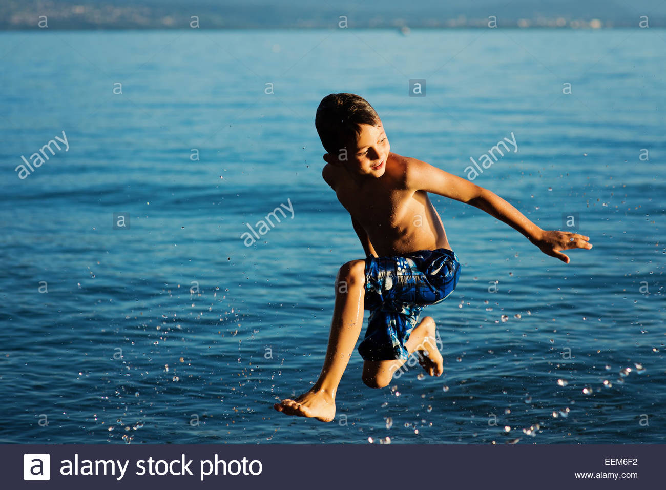 Boy (6-7) jumping into water - Stock Image