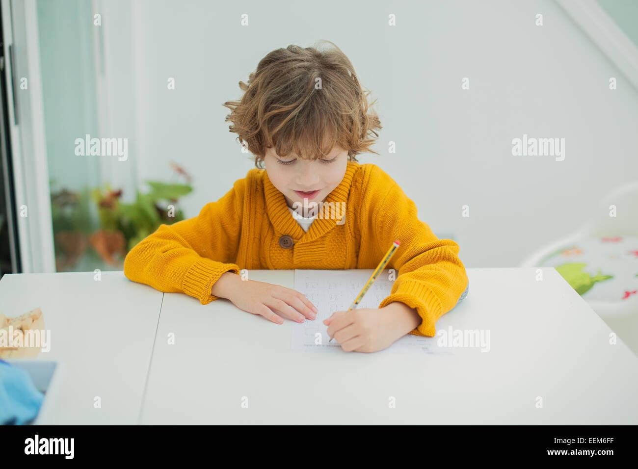 Boy (6-7) doing homework - Stock Image