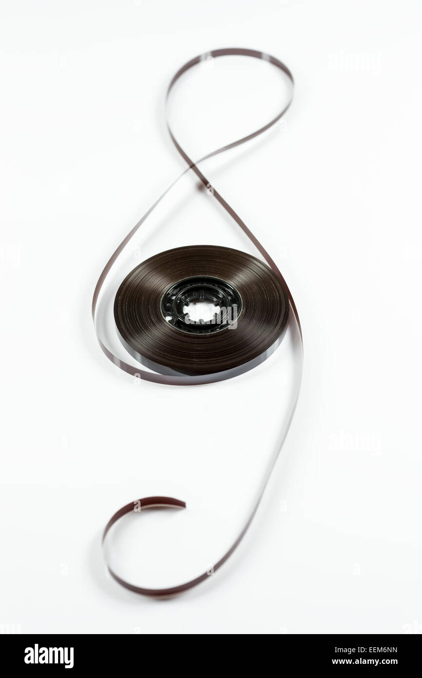 Musical symbol of the G-clef made from audio cassette tape and roller, on white background - Stock Image