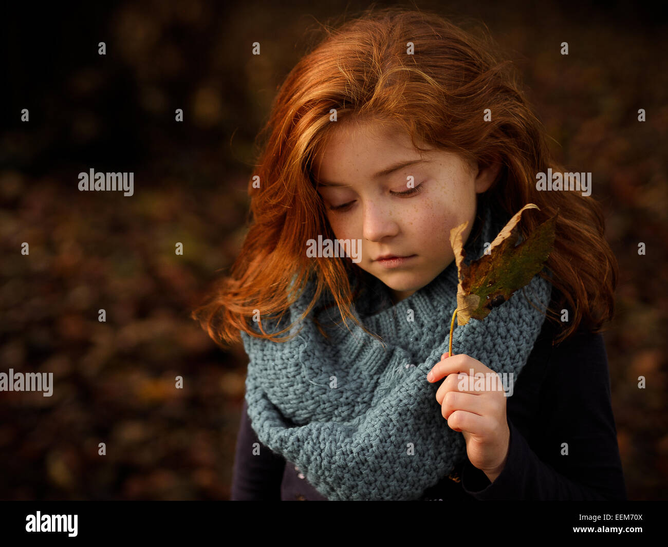Red haired girl holding autumn leaf - Stock Image