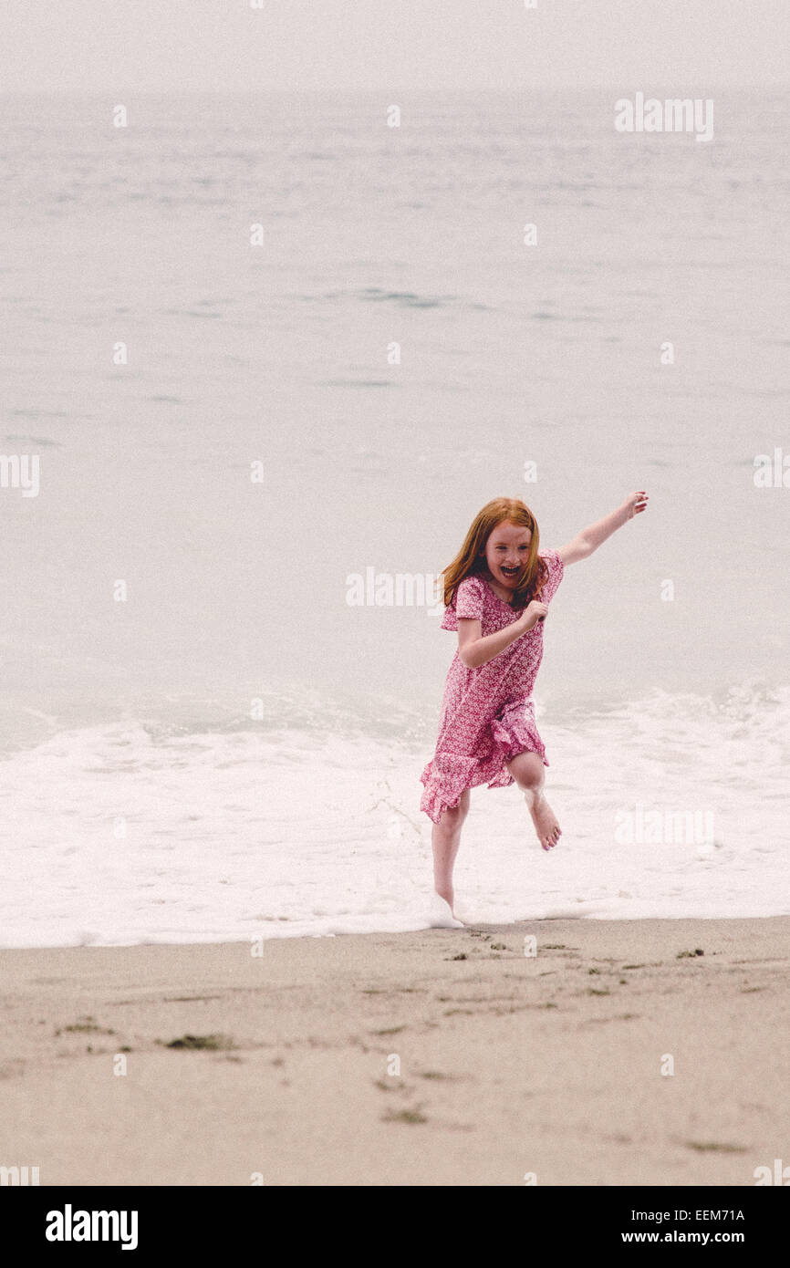 Girl (6-7) running away from waves - Stock Image