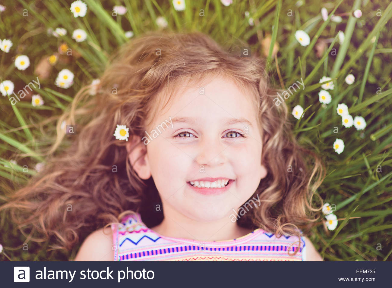 Portrait of smiling girl (4-5) lying in grass - Stock Image