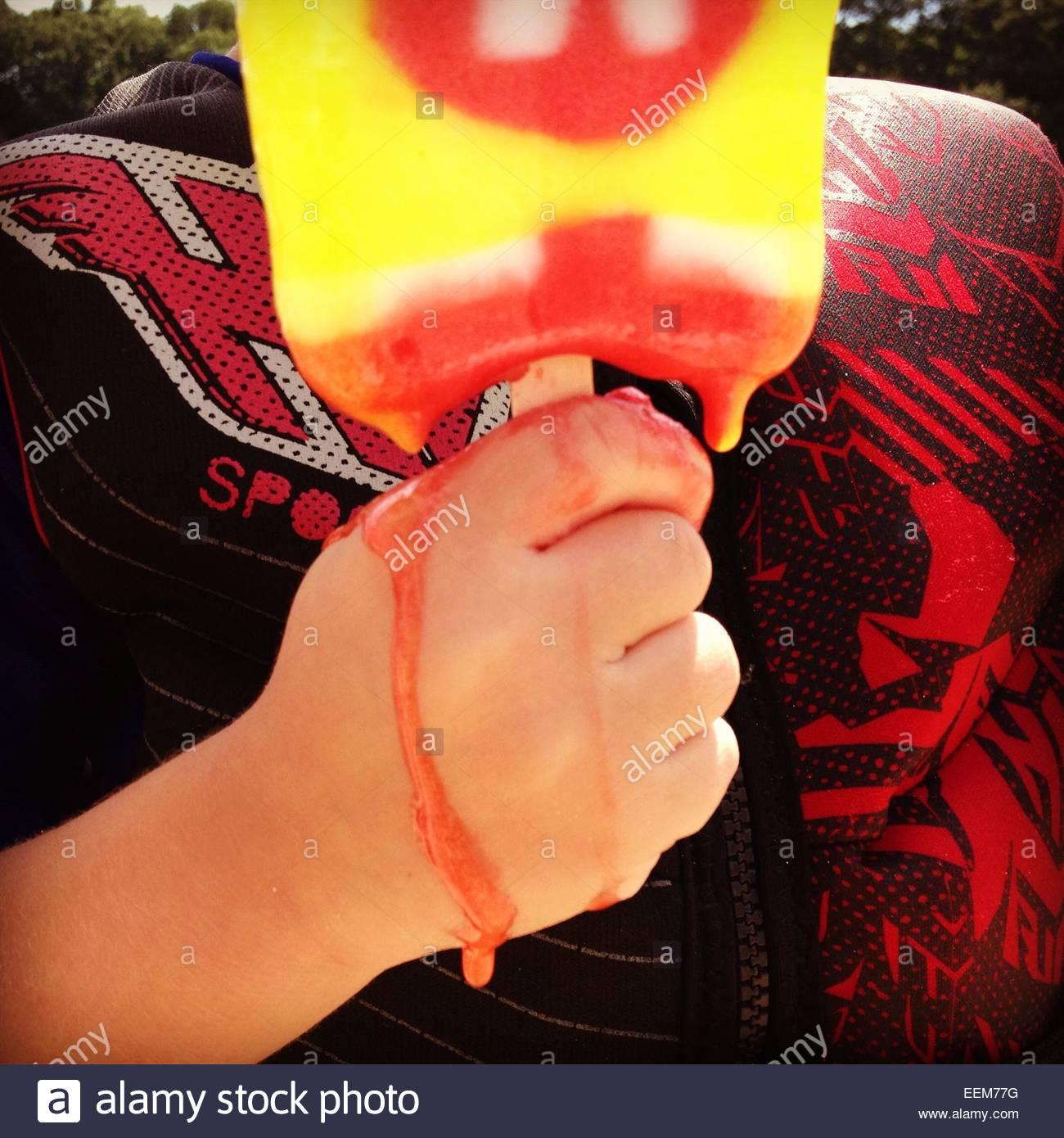 Boy holding melting ice cream bar - Stock Image