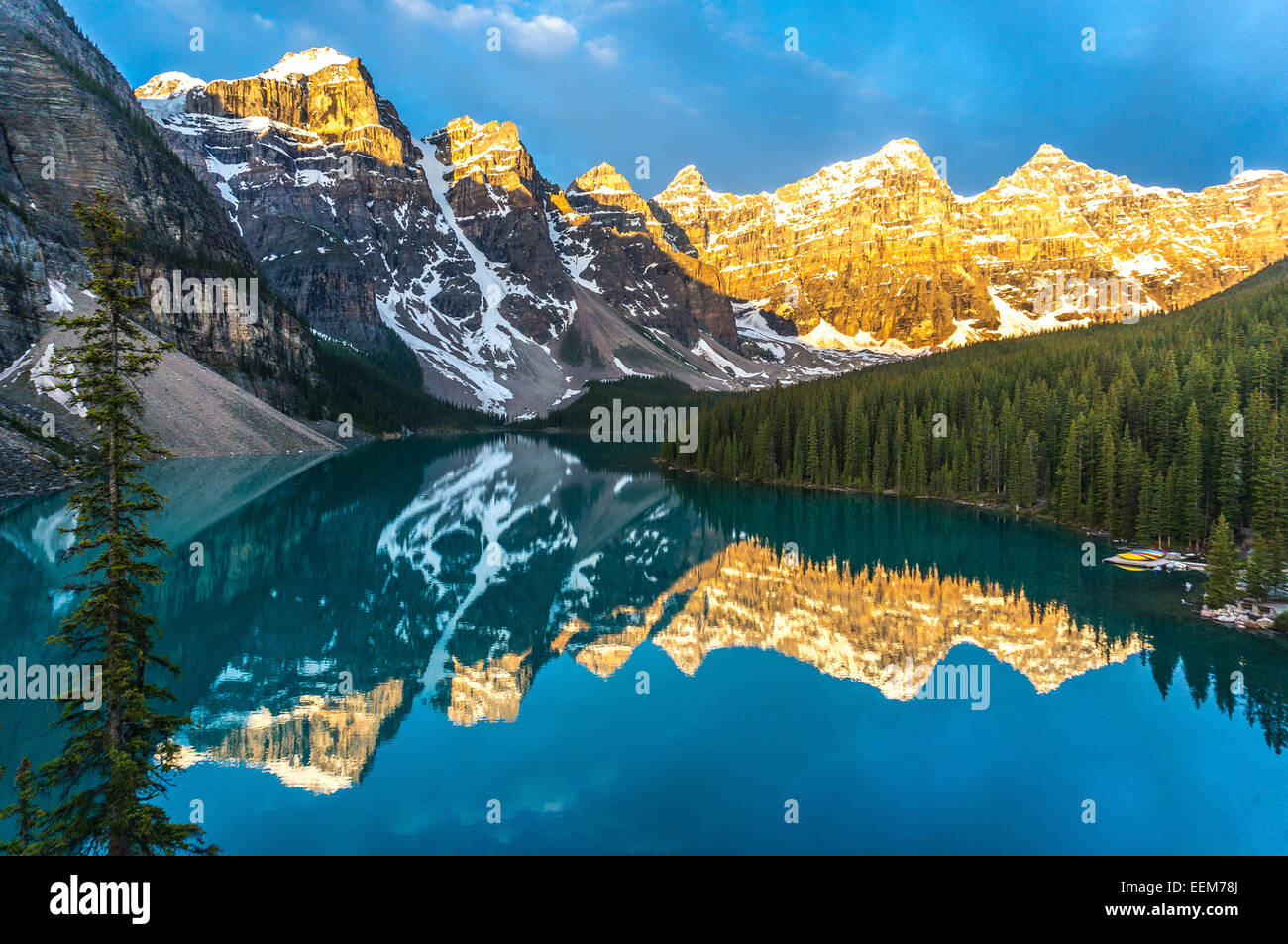 Canada, Banff National Park, Canadian Rockies, Mountains reflecting in calm lake at sunrise - Stock Image
