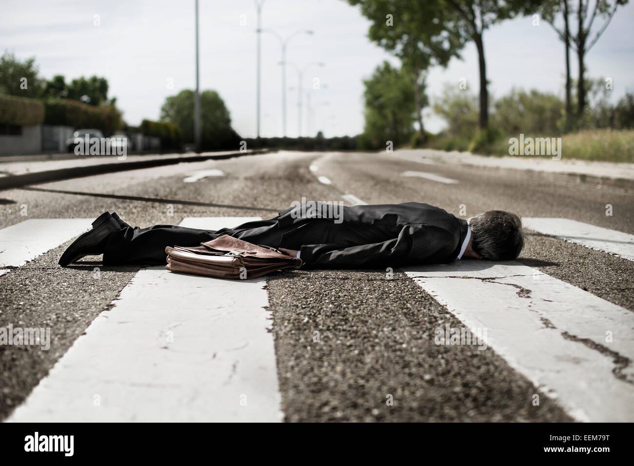 Businessman lying on zebra crossing. - Stock Image