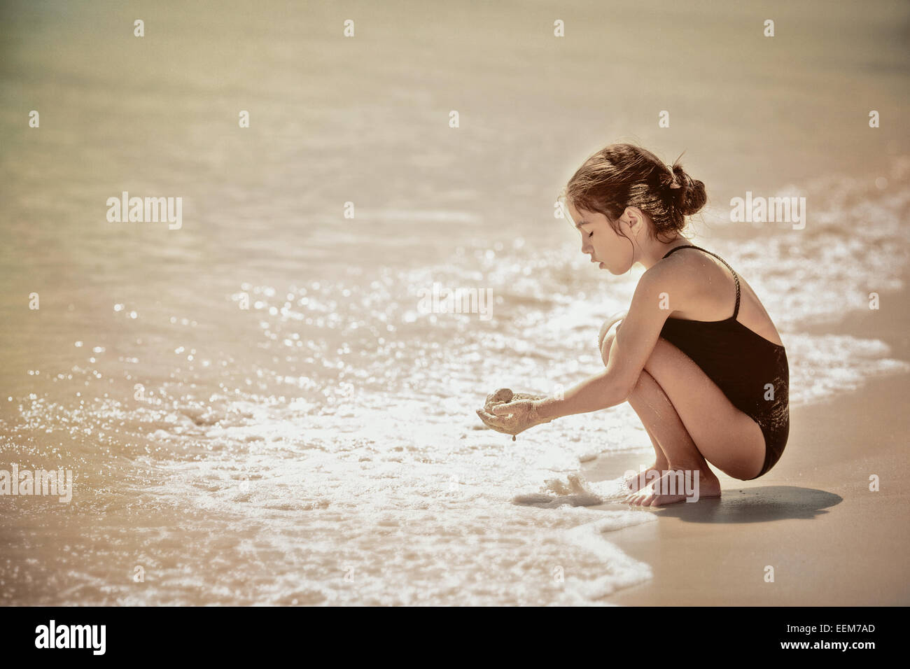 Girl crouching by water's edge on sandy beach and holding wet sand in hands - Stock Image