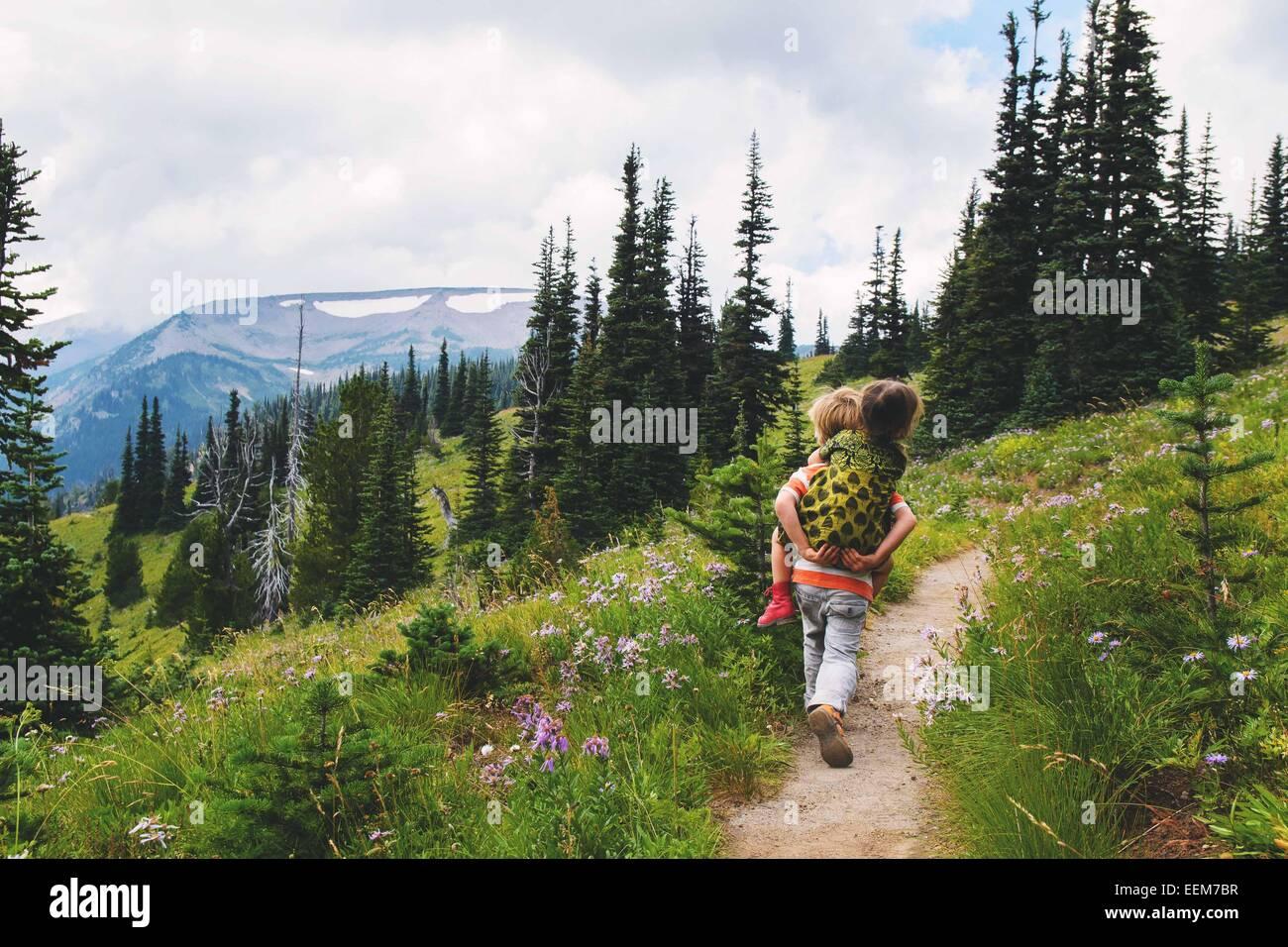 Boy walking along a mountain trail giving his sister a piggyback ride, USA Stock Photo