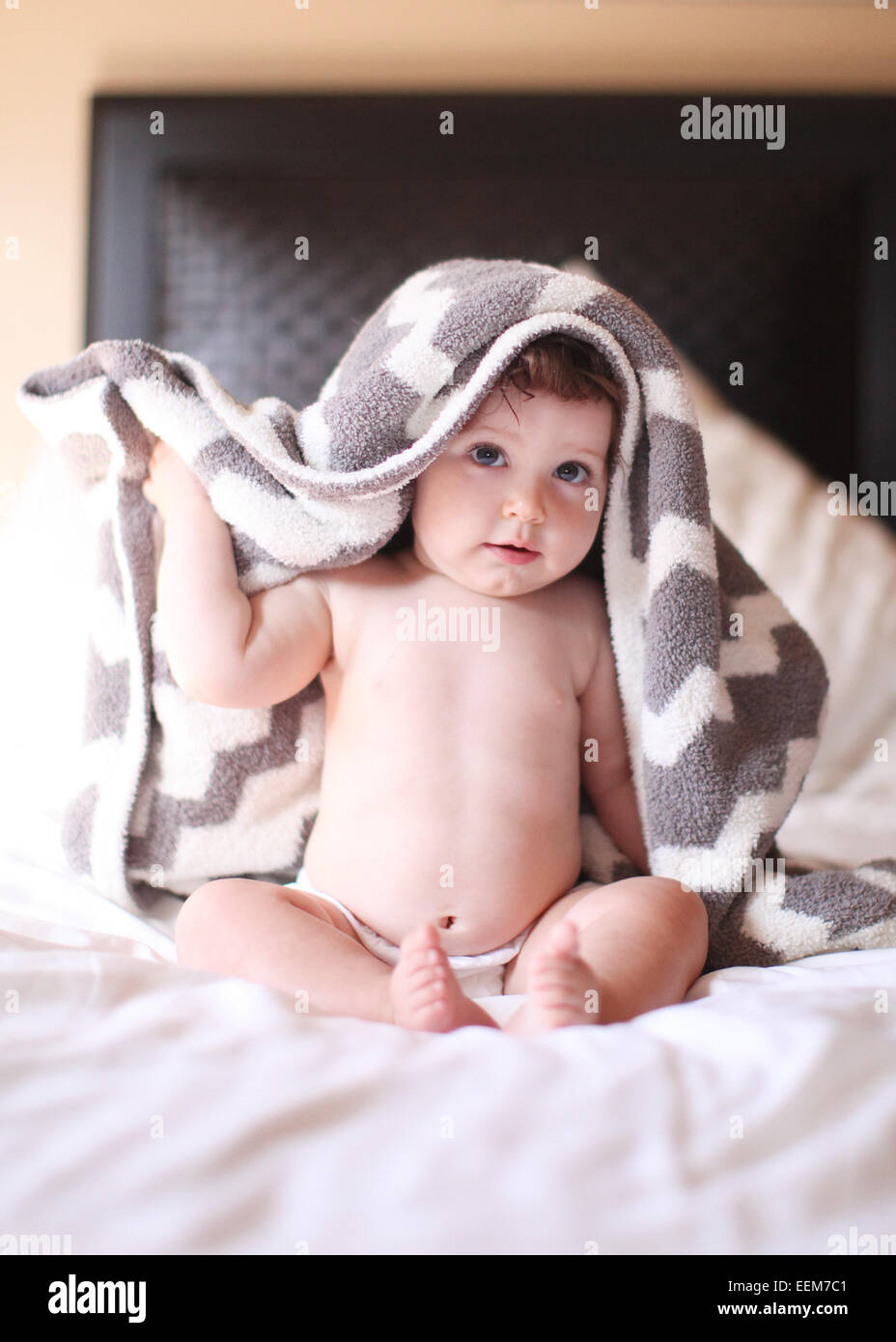 Baby girl covered with towel sitting on bed and looking at camera - Stock Image