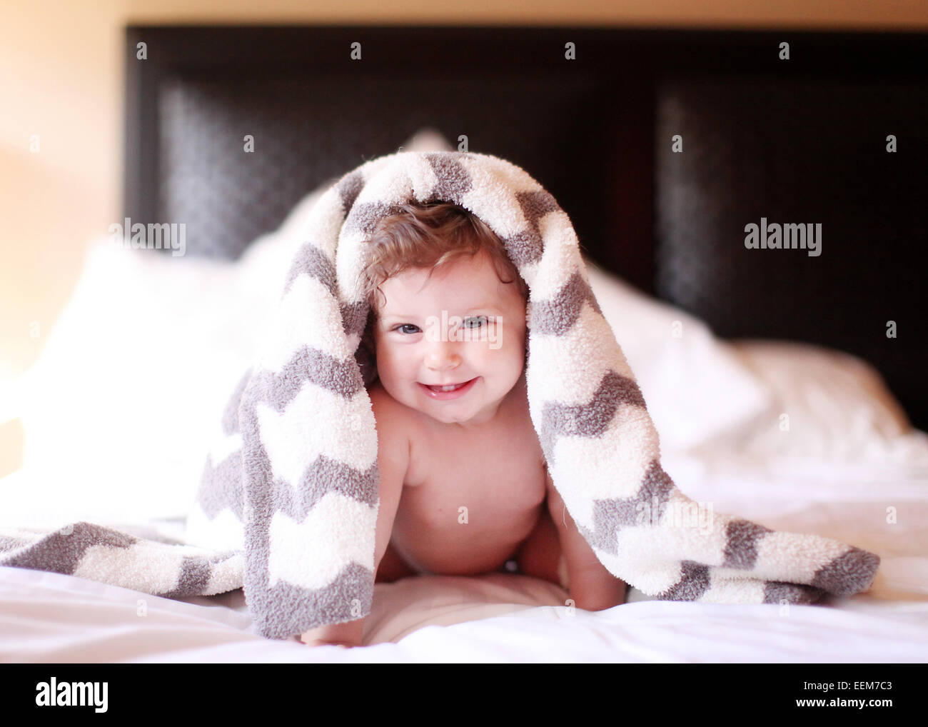 Smiling baby girl sitting on bed under a blanket - Stock Image