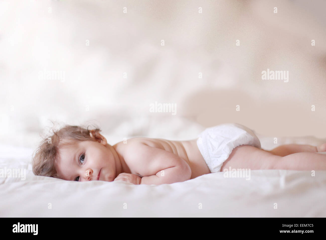 Baby girl lying on bed and looking at camera - Stock Image