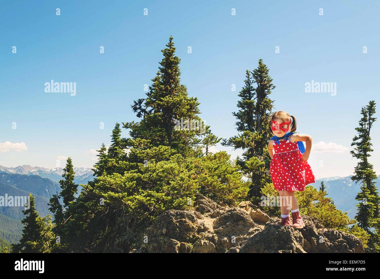 Young girl (2-3) wearing super hero mask and cape standing on top of mountain - Stock Image