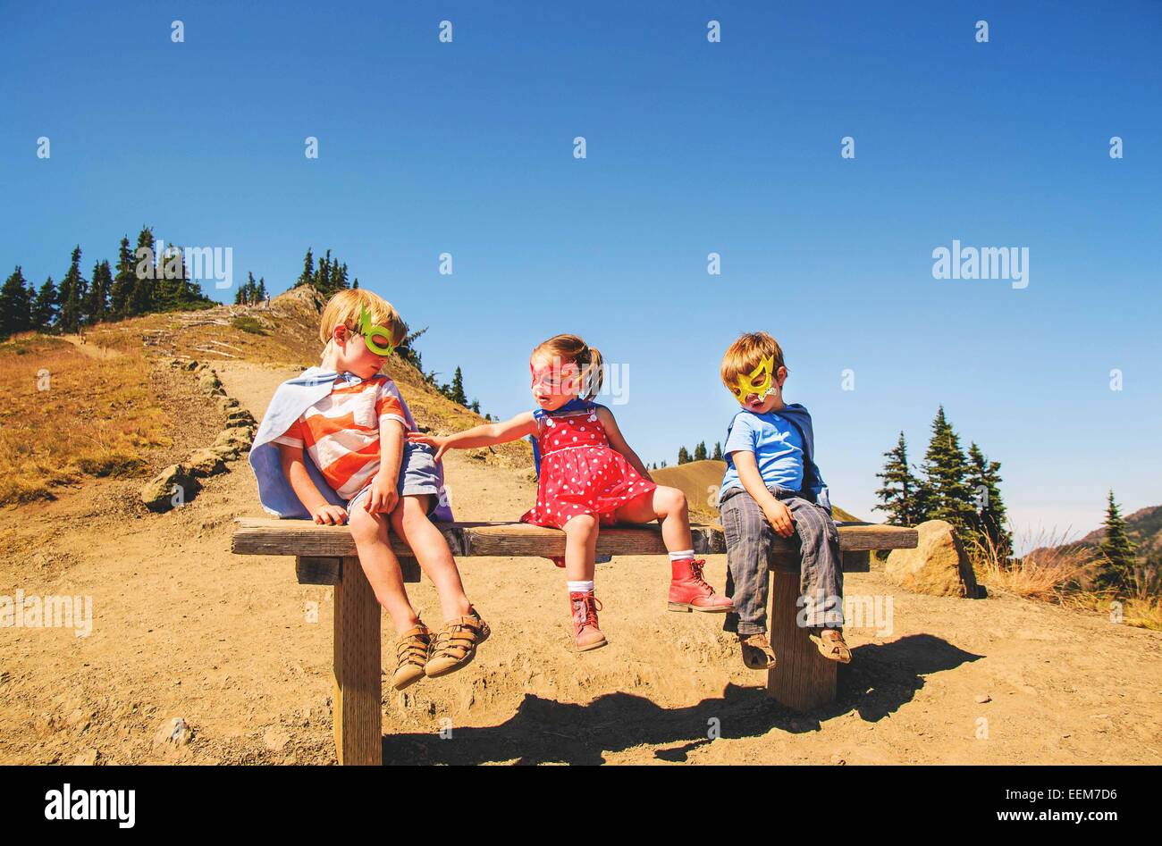 Three children (2-3, 4-5) sitting on bench wearing super hero costumes - Stock Image