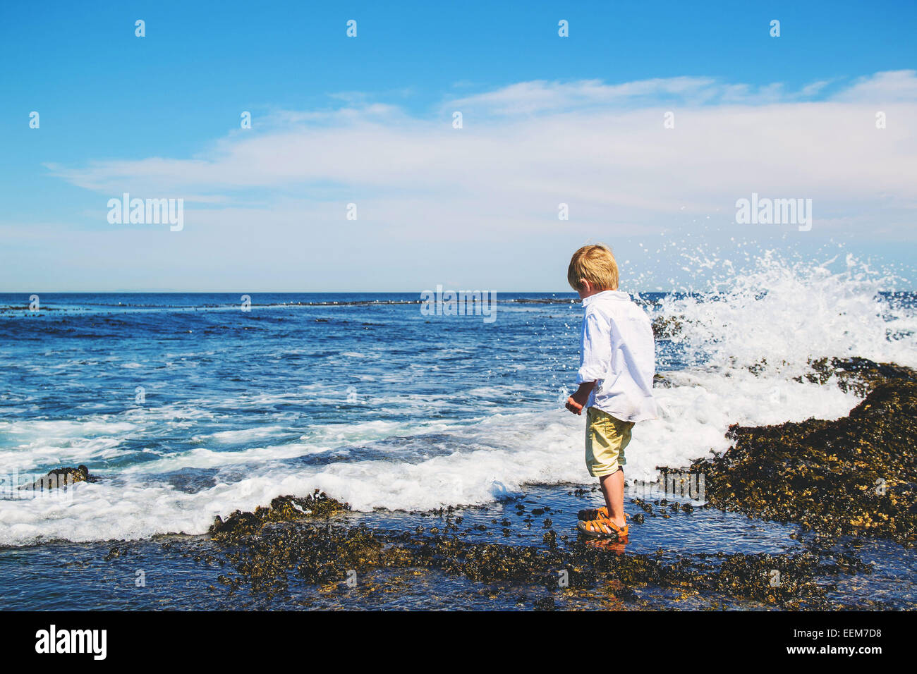 Young boy (4-5) getting splashed by waves - Stock Image