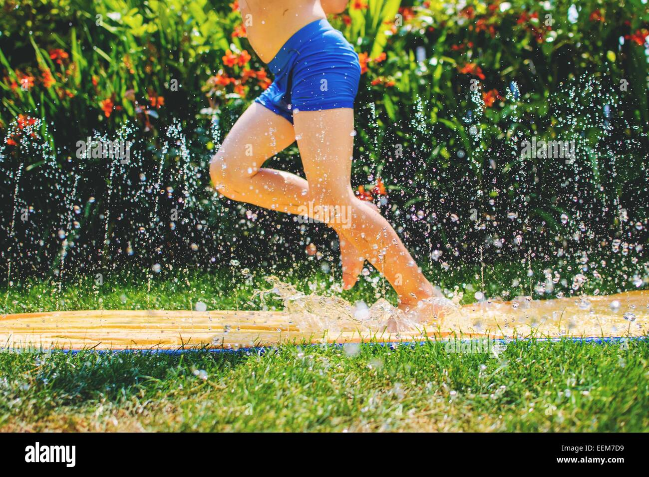 Young boy's legs (4-5) running through water play - Stock Image