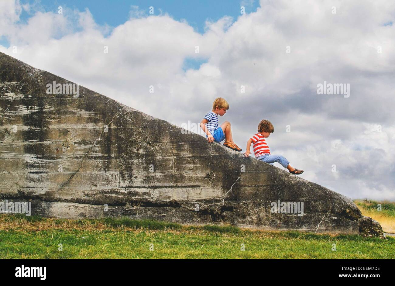 Two young boys (2-3, 4-5) climbing on ledge outside - Stock Image