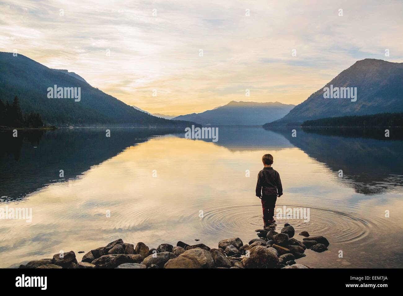 Boy (4-5) standing at water's edge looking at view - Stock Image