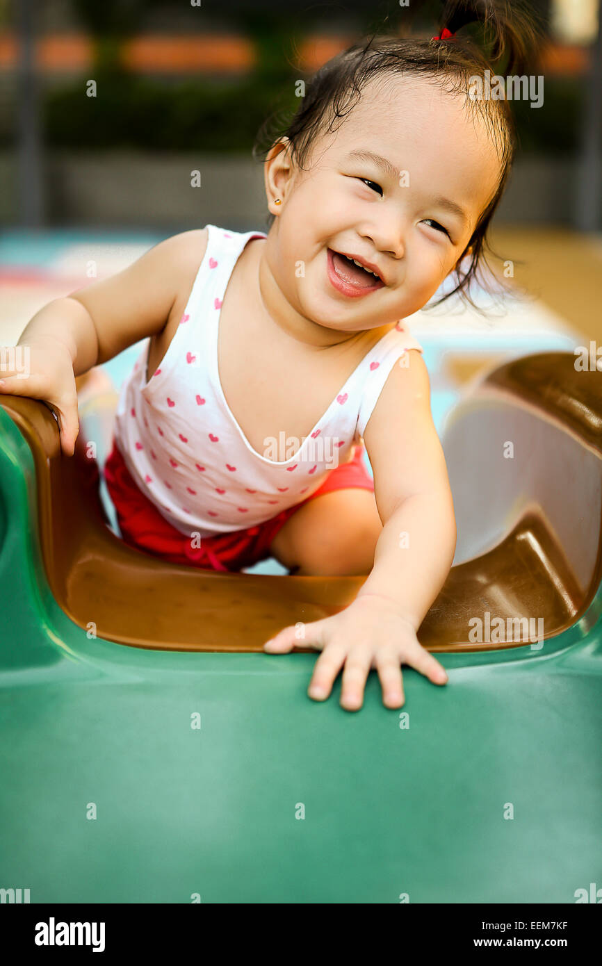 Happy girl (2-3) playing at playground - Stock Image