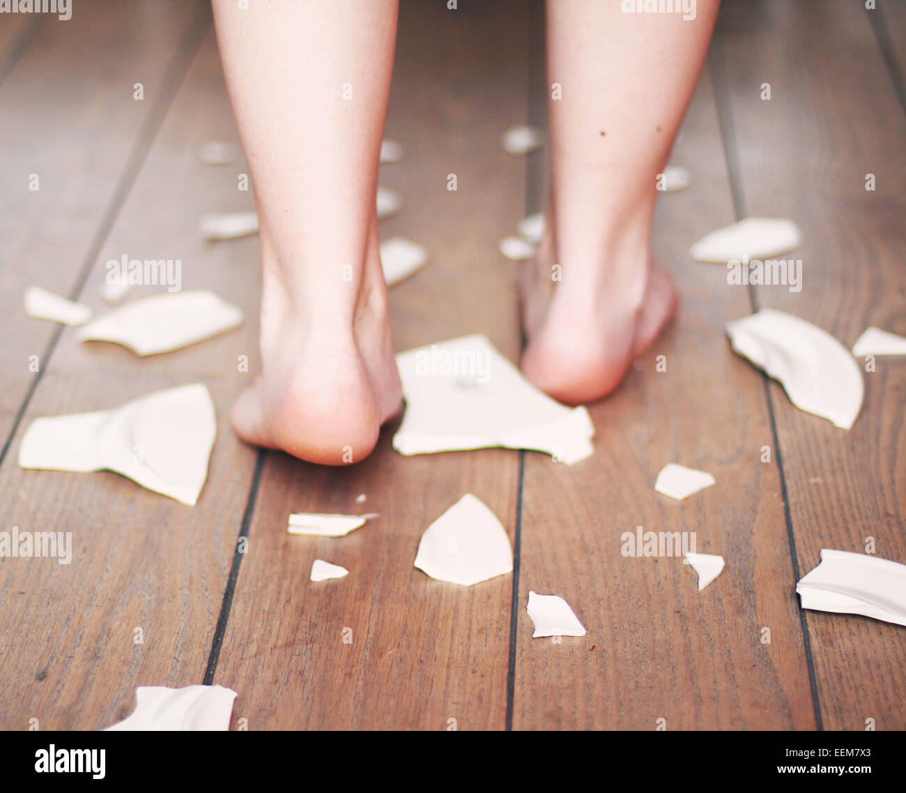 Teenage boy walking among shards of porcelain - Stock Image