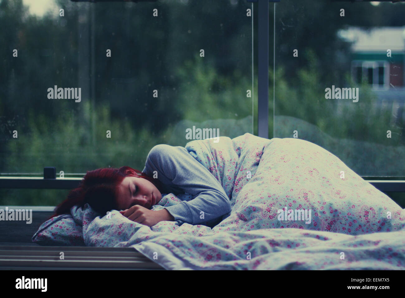 Young woman sleeping at bus shelter - Stock Image
