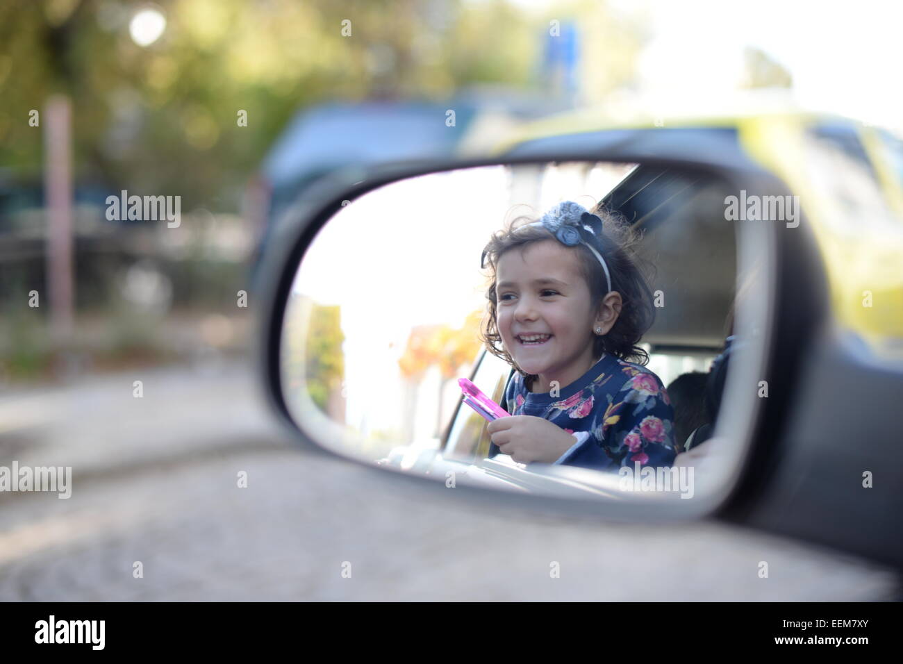Girl (4-5) enjoying car trip and looking in rearview mirror - Stock Image