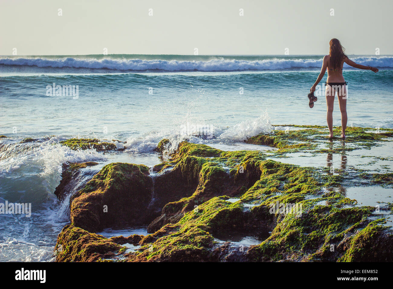 Indonesia, Bali, Woman standing in front of sea Stock Photo
