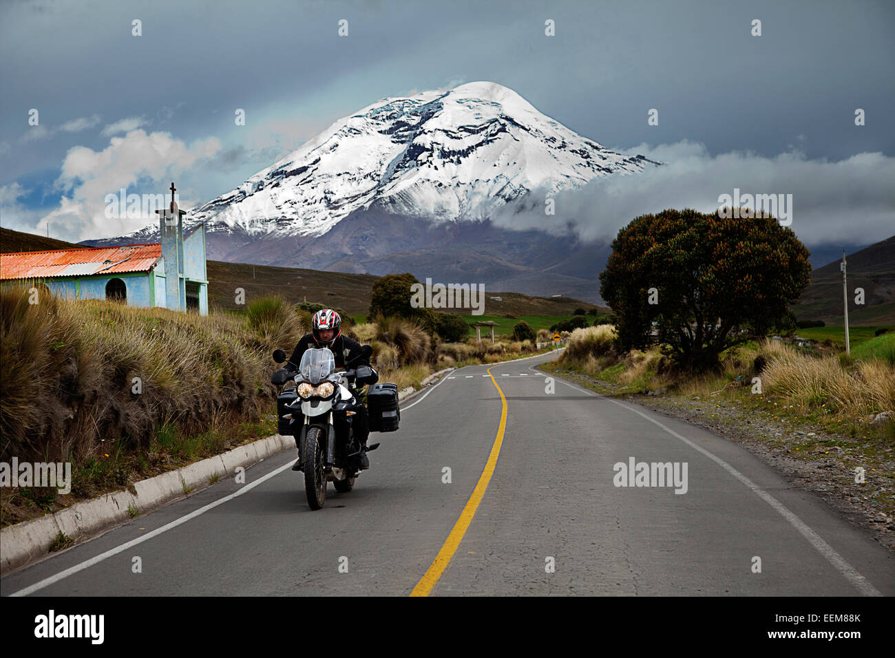 Ecuador, View of man riding motorbike with Chimborazo volcano in background Stock Photo