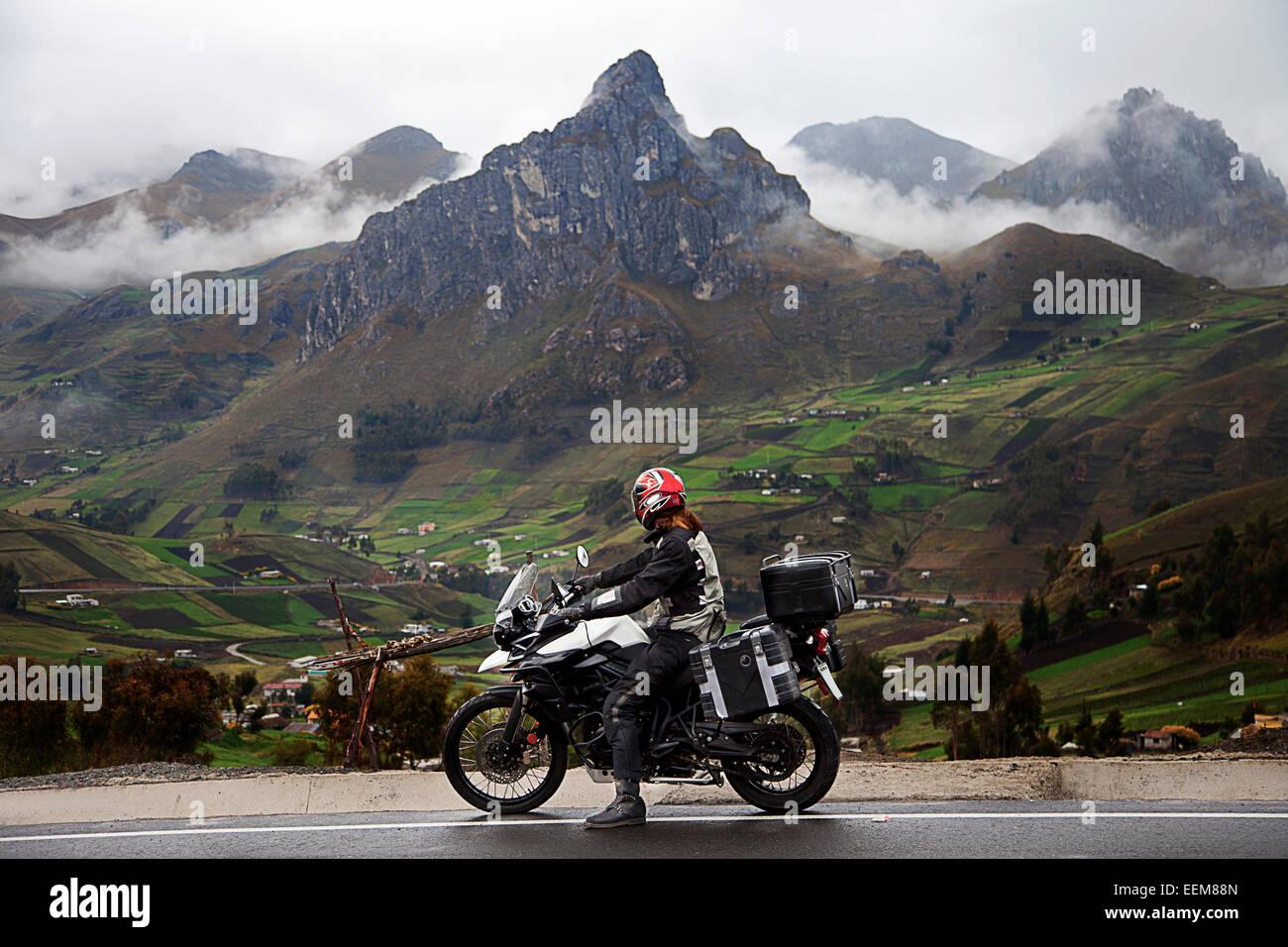 Ecuador, Man on bike on roadside with mountain range in background - Stock Image