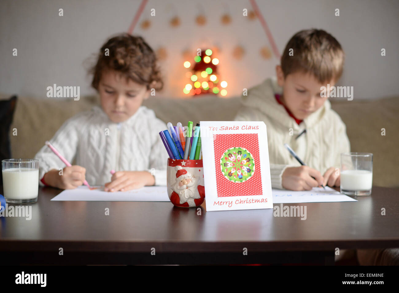 Brother (6-7) and sister (4-5) writing letter to Santa Claus - Stock Image