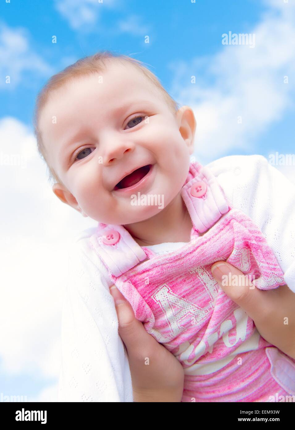 Baby girl (6-11 months) reaching for sky - Stock Image