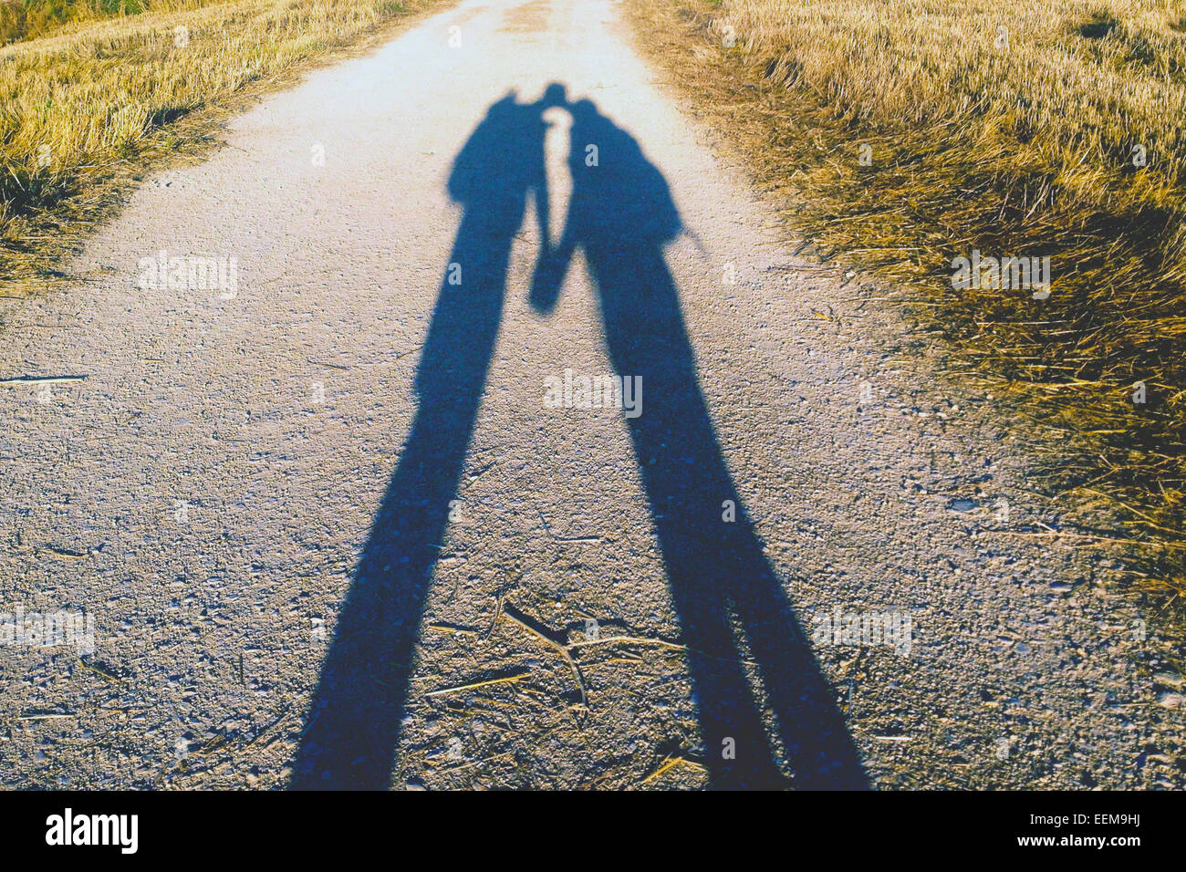 France, Camino de Santiago, Shadow of hiker couple on country road - Stock Image