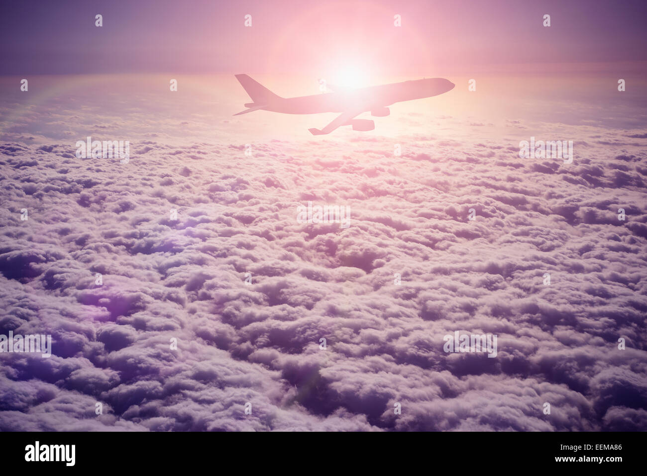 Silhouette of airplane flying over clouds Stock Photo