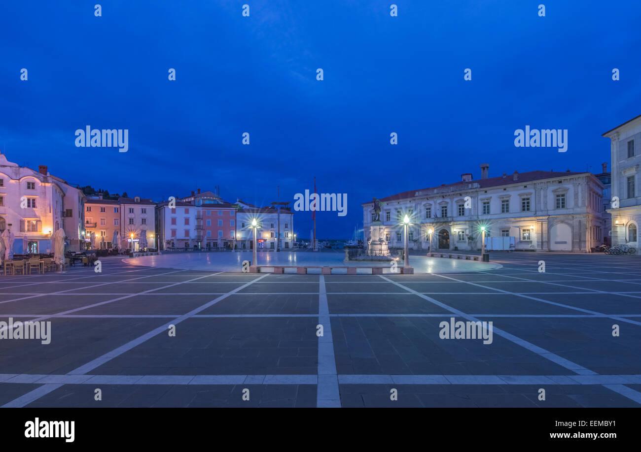 Buildings and town square illuminated at night, Piran, Coastal-Karst, Slovenia - Stock Image