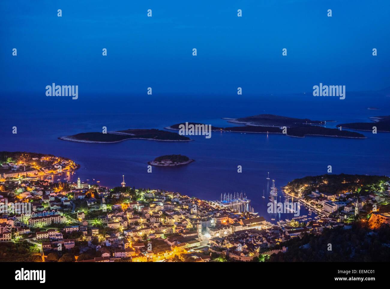 Aerial view of coastal town illuminated at night - Stock Image