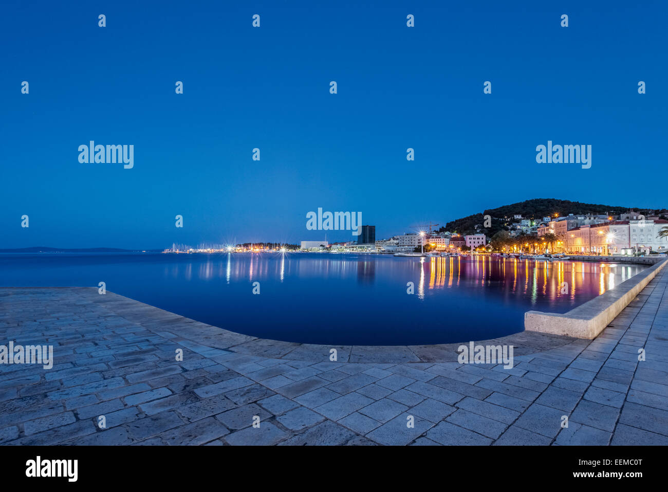 Waterfront sidewalk, illuminated boats and dock at dusk, Split, Split, Croatia - Stock Image