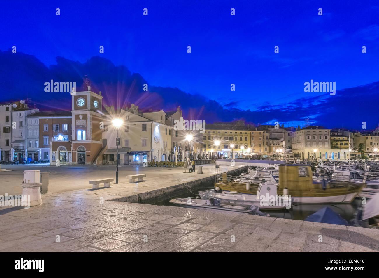 Illuminated waterfront promenade and dock at night, Rovinj, Istria, Croatia - Stock Image