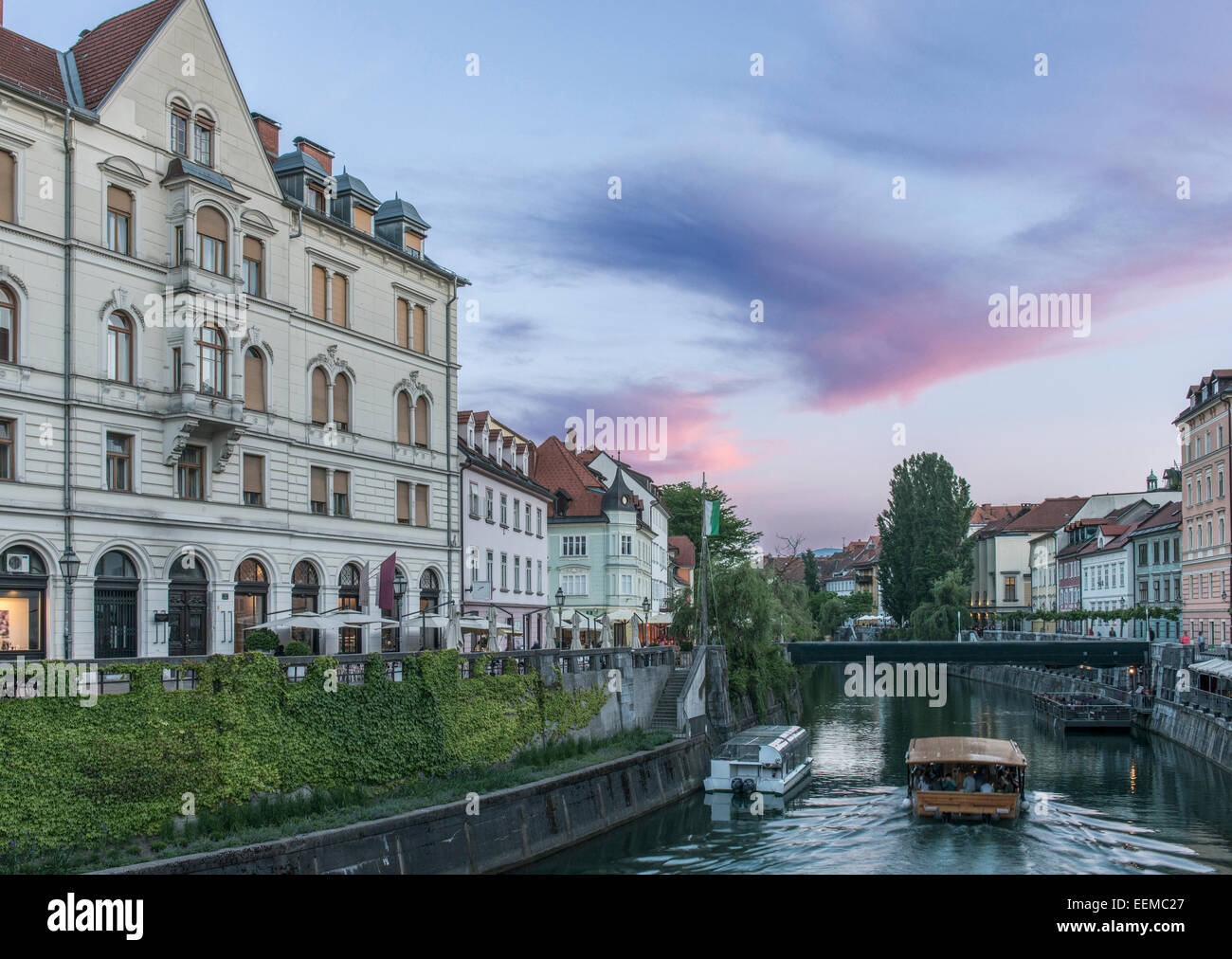 Buildings and pedestrian bridge over urban canal, Ljubljana, Central Slovenia, Slovenia - Stock Image